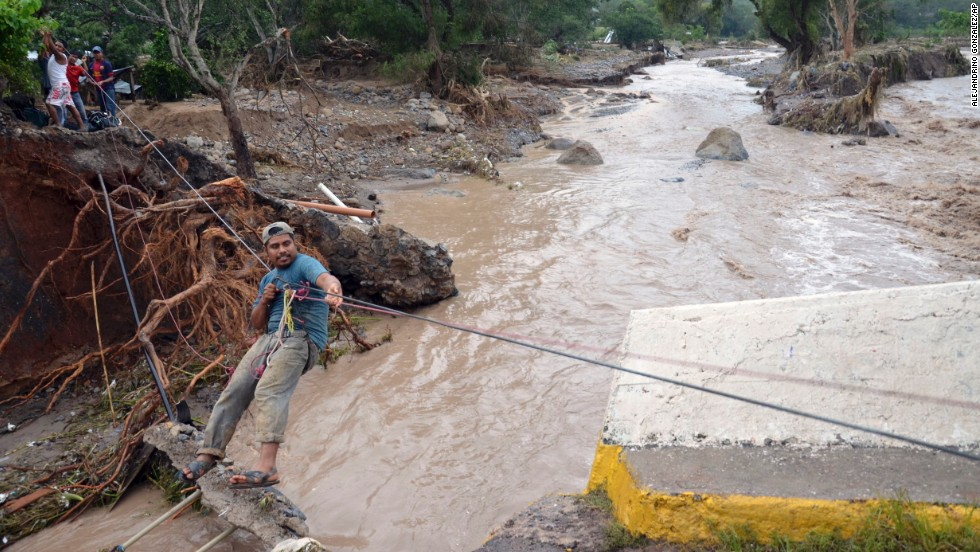 A man crosses a river using a makeshift zip line on September 18, after a bridge collapsed near the town of Petaquillas, Mexico.