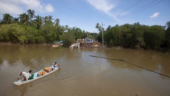 A boat moves across the Papagayo River to ferry people from the end of a collapsed bridge in Acapulco on September 18.