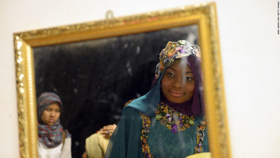 Obabiyi Aishah Ajibola of Nigeria checks her makeup in a mirror during the competition.