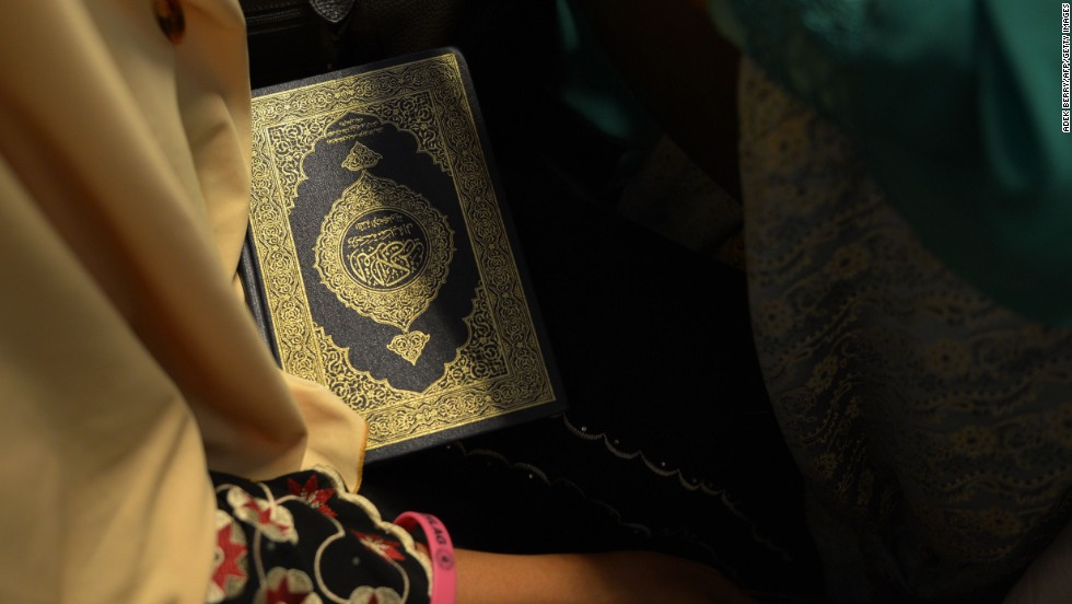 A contestant holds a copy of the Quran backstage.