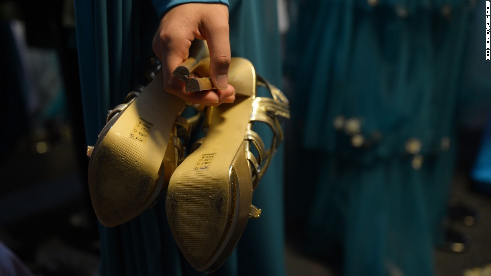 A contestant holds a pair of shoes backstage.