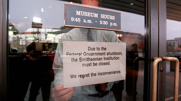 An employee hangs a sign on the door of the Smithsonian