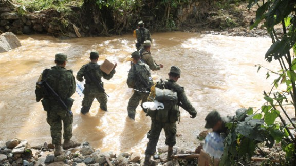 Members of the military try to move aid to Atoyac de Alvarez, which is isolated because of flooding on September 19.