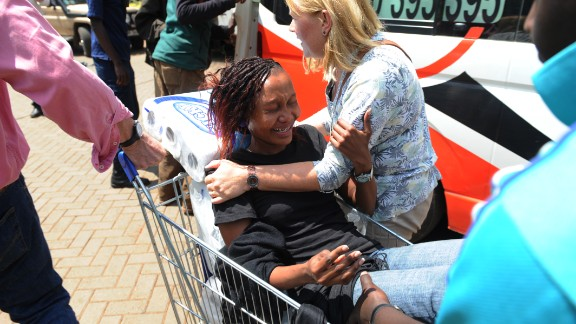 A woman is pulled by a shopping cart to an ambulance.
