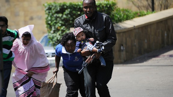 A policeman carries a baby to safety after masked gunmen stormed an upmarket mall and sprayed gunfire on shoppers and staff, killing at least six on September 21, 2013 in Nairobi. The Gunmen have taken at least seven hostages, police and security guards told an AFP reporter at the scene. AFP PHOTO/SIMON MAINA        (Photo credit should read SIMON MAINA/AFP/Getty Images)