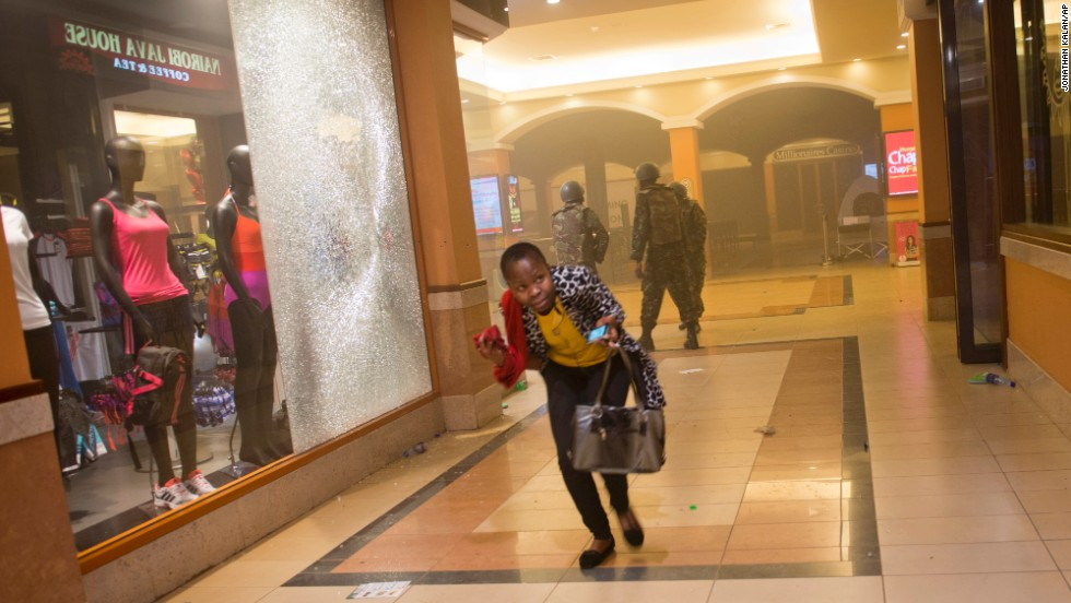 A woman who had been hiding during the attack runs for cover after armed police enter the mall.