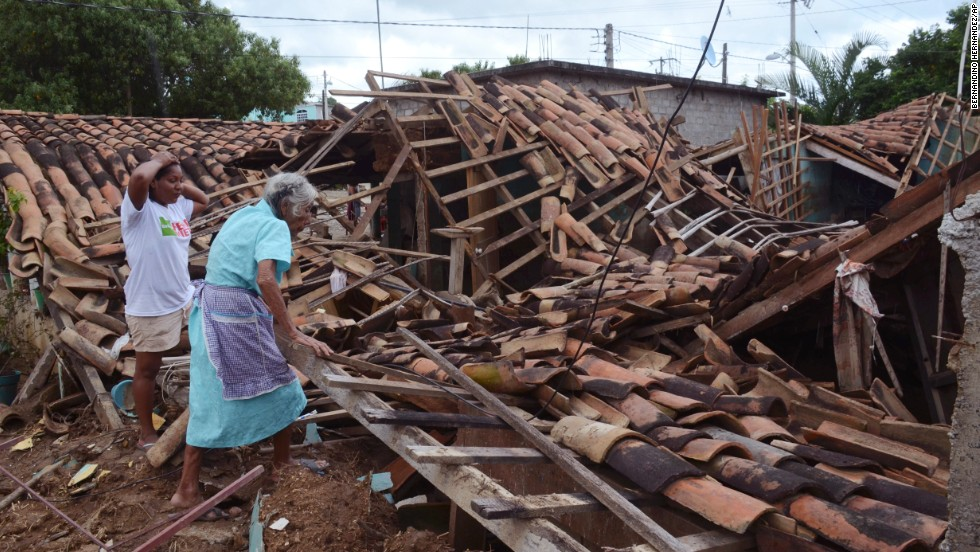 Two women inspect what is left of their home in the village of Salsipuedes, Mexico, on Friday, September 20.