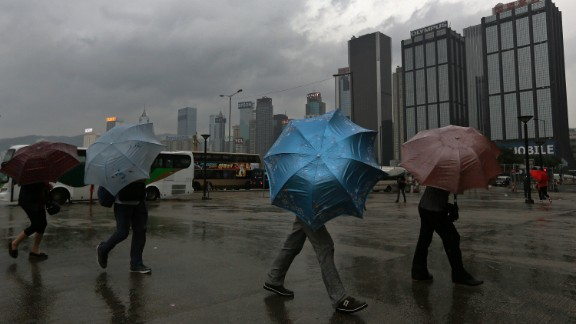 Tourists hang on to their umbrellas near the waterfront in Hong Kong on September 22.