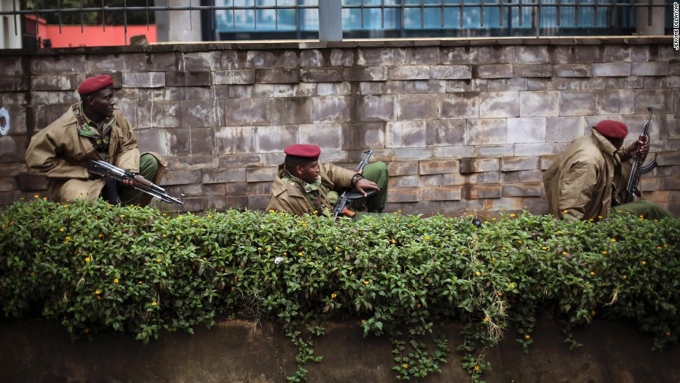 Kenyan security forces crouch behind a wall outside the mall on September 23.