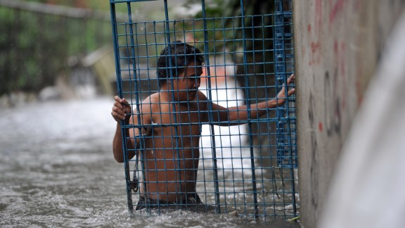 A resident closes the gate of his flooded home in Manila after torrential rains pounded Luzon island on September 23.
