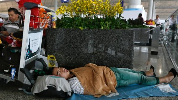 A passenger sleeps at Hong Kong's international airport as flights are delayed on September 23.
