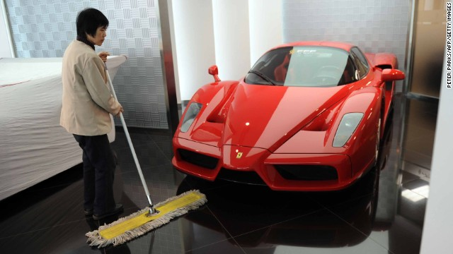 A 2011 file photo of a cleaner sweeping the floor next to a Ferrari in a  Beijing luxury car showroom.