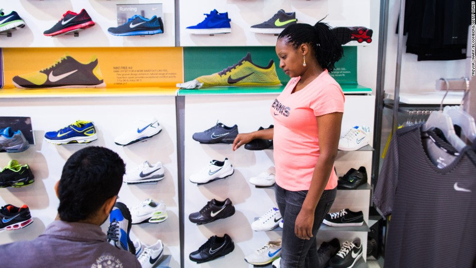 An employee, right, assists a customer selecting sports shoes at a Nike retail outlet inside the mall.