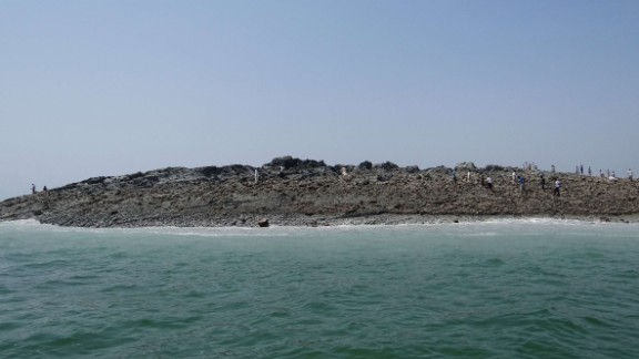 People walk on an island that formed off the coastline of Gwadar after the earthquake hit in this photo released by the Pakistani government.