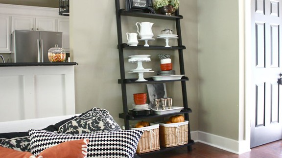 "Sarah Macklem loves to entertain, so she decorated the bookshelf in her living room with seasonal dishes and barware, including a new set of tarnished, vintage silver wine glasses that are ""just waiting to be filled with Witch's Brew wine,"" she said. Want to know more about this style of bookshelf? Ask Macklem in the comments section below."