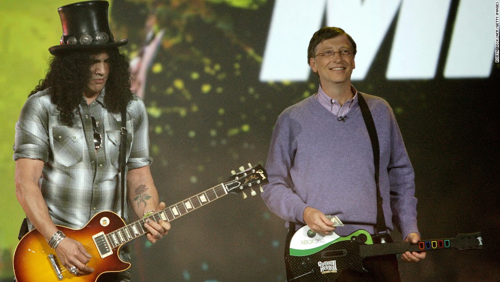 Rockin'! Gates plays the Guitar Hero video game as legendary Guns 'N' Roses guitarist Slash plays a real guitar at the 2008 Consumer Electronics Show.
