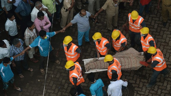 Personnel from the National Disaster Relief Force carry a body from the site of the collapse on September 28.