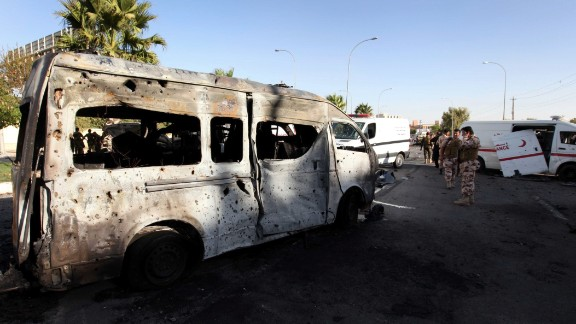 Security forces inspect the site of a car bomb explosion in Iraq
