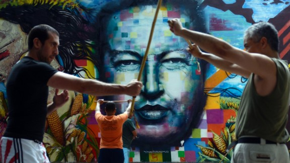 People train stick fight in front of a mural depicting late Venezuelan former President Hugo Chavez, August, 18, 2013.