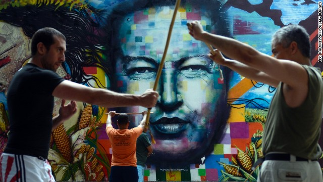 People train stick fight in front of a mural depicting late Venezuelan former President Hugo Chavez in Caracas on August, 18, 2013.