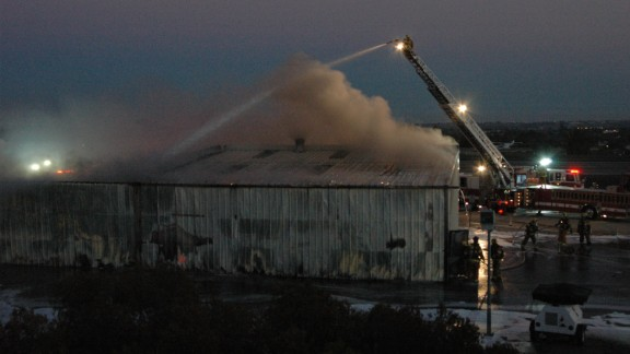 Firefighters pour water on a hangar after a plane crashed into it Sunday night in Santa Monica, California.