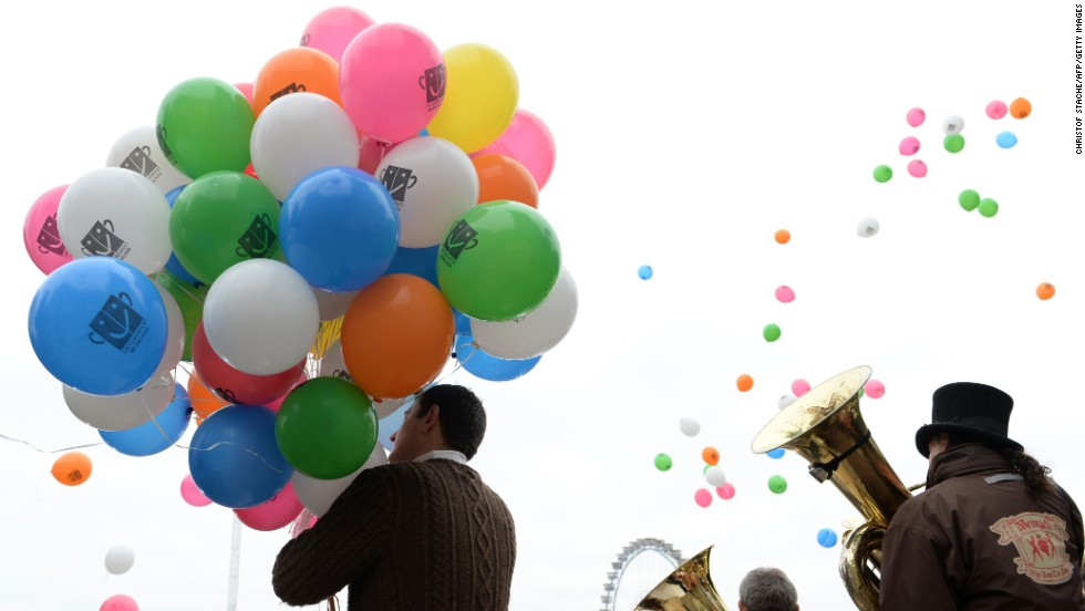 A man holds balloons as brass players perform in Munich on September 29.