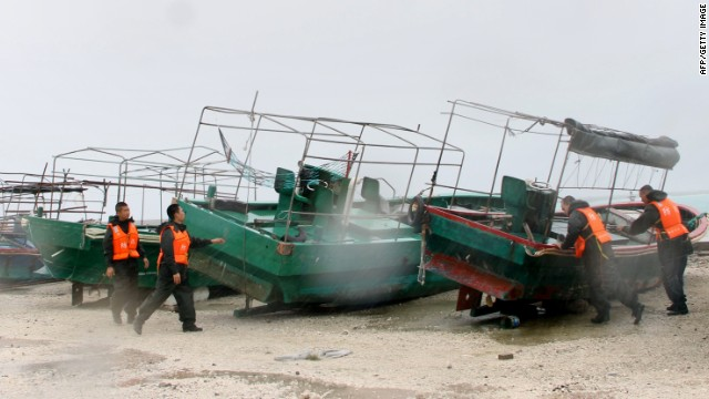 Emergency personnel work to secure fishing boats parked in a harbor on Yongxing island, on Sunday, September 29.