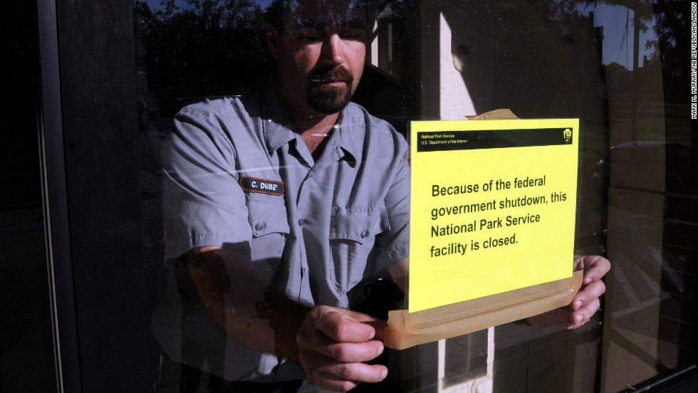 An employee at the Springfield Armory National Historic Site in Springfield, Massachusetts, puts up a sign on October 1, to notify visitors that the site is closed because of a government shutdown.