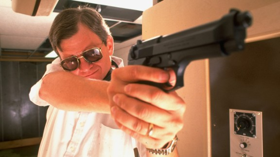 Clancy poses with his pistol during target practice in his private underground pistol range in Maryland in 1989.