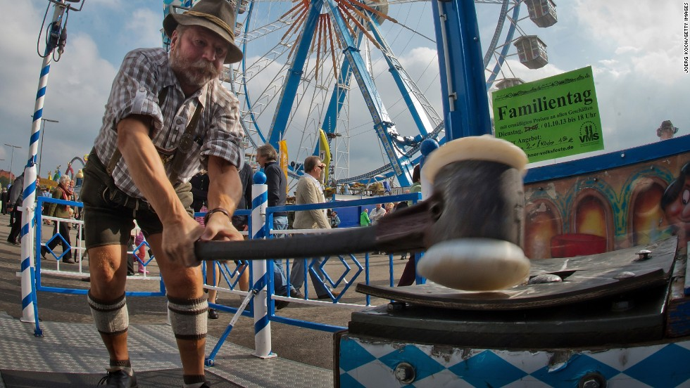 "A man swings a hammer down on a ""strong man"" game at the festival on Tuesday, October 1."
