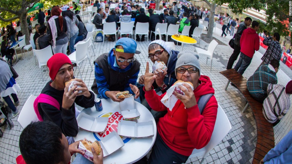 Fast-food fans tuck in to a first Burger King meal from the chain's Cape Town restaurant, which opened its doors in May 2013.