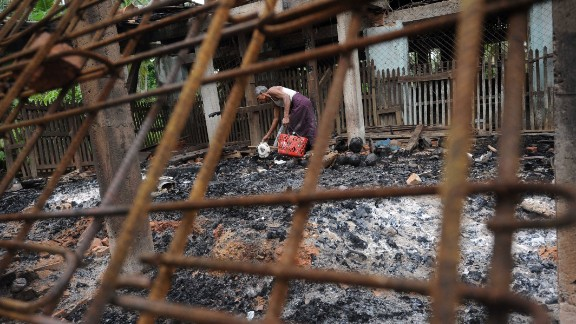 A man salvages items from the burnt area of a mosque following communal clashes in Thabyu Chi village near Thandwe, in Myanmar