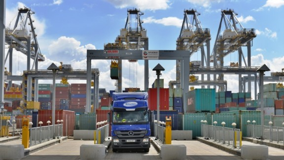 A lorry waits in a loading bay at London Gateway while a ship is unloaded in the background.