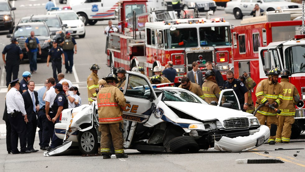 Rescue personnel stand around a smashed U.S. Capitol Police cruiser near the Capitol.