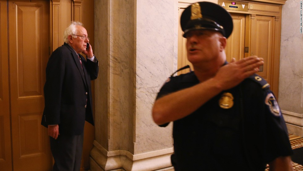 Sen. Bernie Sanders speaks on the phone at the Capitol.