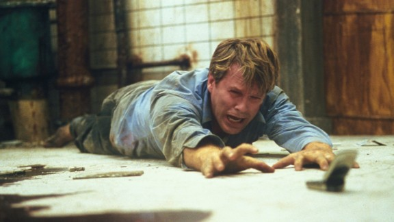 """For almost the entire running time of """"Saw"""" (2004), a corpse lies in a pool of blood on the floor of well-hidden washroom. Meanwhile, two chained figures, played by Cary Elwes and Leigh Whannell, realize they're part of a brutal serial killer's game. After much gore and misdirection, the serial killer is revealed to be the corpse -- who's not so dead after all."""