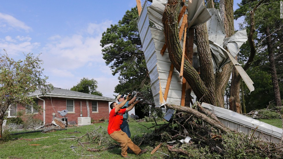 Residents try to free a house panel from where it was lodged against a tree following a tornado in Bennet, Nebraska, Friday, October 4. Powerful storms struck the Midwest on Friday, dumping heavy snow in South Dakota, spawning a tornado in Nebraska and threatening dangerous thunderstorms from Oklahoma to Wisconsin.
