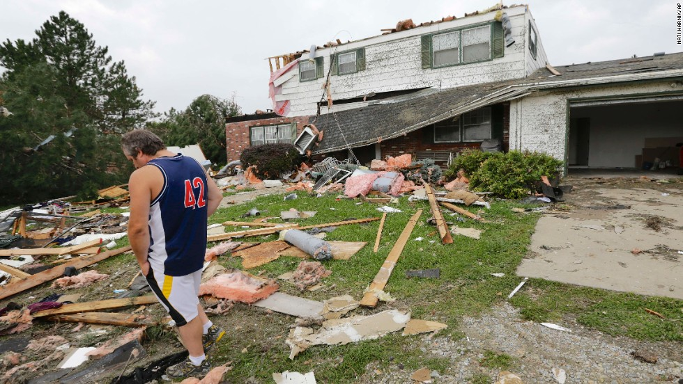 Travis Randall walks through the debris-strewn yard of his parent's home in Hickman, Nebraska, on October 4 after it was struck by a tornado.
