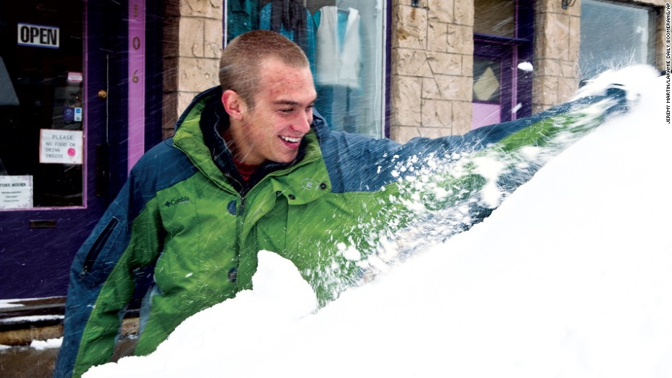 Sam Cornia brushes snow off of the windshield of his car on October 4 in Laramie, Wyoming.
