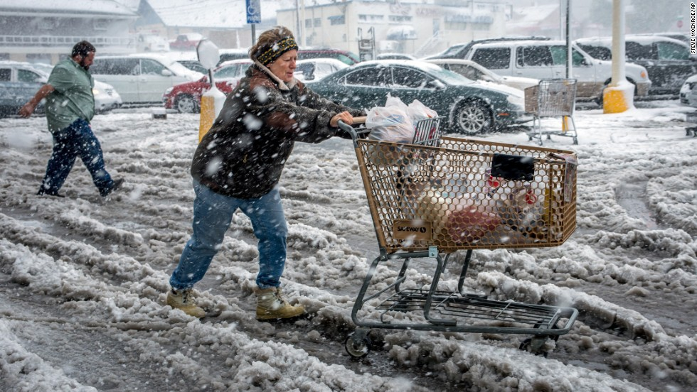 Brenda Nolting, of Rapid City, South Dakota, rolls her cart to her car after stocking up on necessities on October 4.