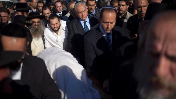Israeli Prime Minister Benjamin Netanyahu, center, escorts Yosef's body during the rabbi's funeral in Jerusalem on October 7.