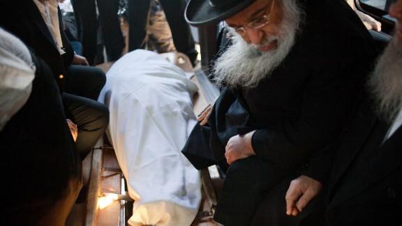 Orthodox Jews sit next to the rabbi's body on October 7 in Jerusalem.