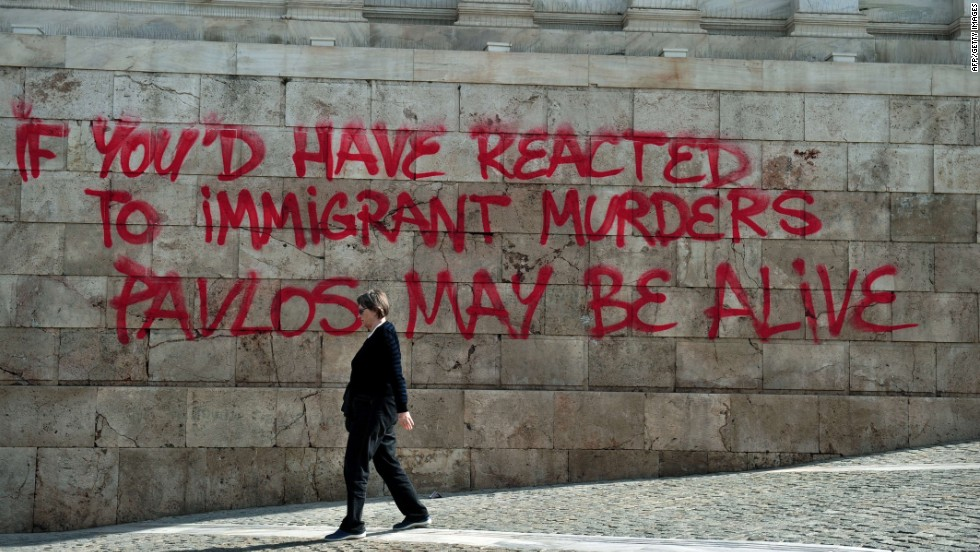 A woman walks past graffiti sprayed on the Athens Academy building in reference to the murder of anti-fascist musician Pavlos Fyssas on October 4, 2013, allegedly by a Golden Dawn sympathizer. The killing prompted a crackdown on the party.