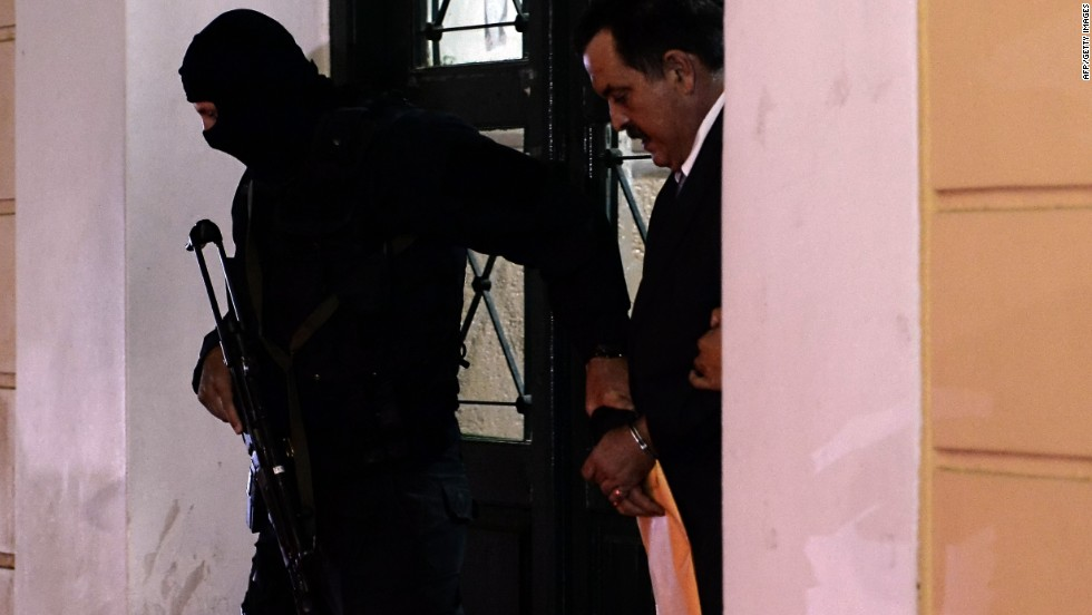 Pappas is escorted by a policeman after a hearing at the Athens court on October 3, 2013.