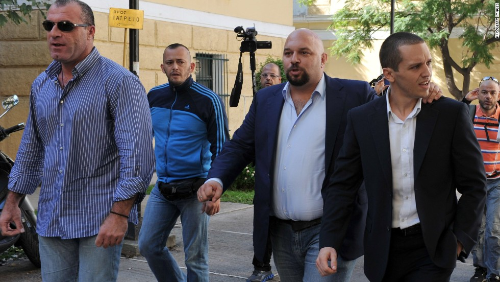Extreme-right Golden Dawn party lawmakers Nikos Michos (L), Ilias Panagiotaros (C) and Ilias Kasidiaris leave a courthouse after being released on October 2, 2013 in Athens, Greece.