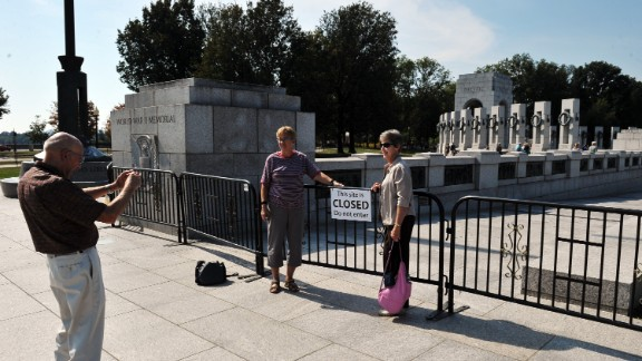 Tourists take photos at a barricade blocking access to the World War II Memorial in Washington on Sunday, October 6.
