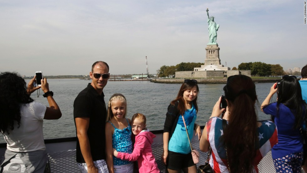 Tourists take photos of the Statue of Liberty while riding a tour boat in New York Harbor on October 3. The statue is adminstered by the National Park Service and is closed as a result of the government shutdown.