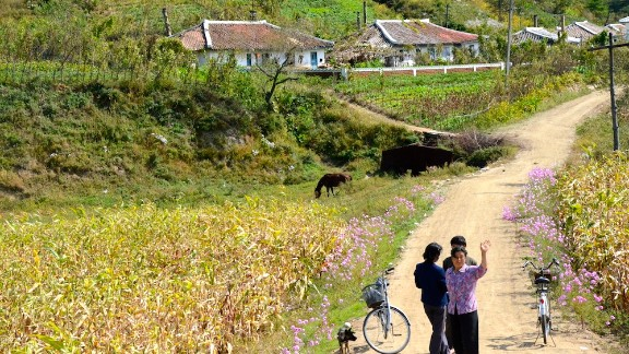Villagers waving by the race path.