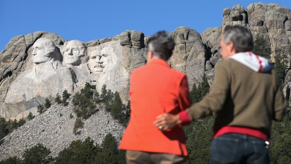Georgia and Keith Ormand stop to take a picture near the entrance to Mount Rushmore National Memorial in Keystone, South Dakota, on October 1. Traffic cones were put up for a short time at a pull-off where people could view the monument. Some said it was to deter tourists from stopping.
