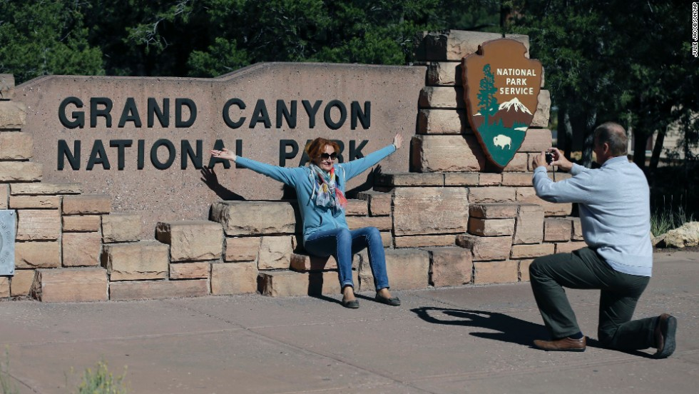 Austrian tourist Ryszard Skrzypek snaps a photo of his wife, Walendowska Malgorzata, close to the entrance to Grand Canyon National Park near Tusayan, Arizona, on Friday, October 4. Park officials have written citations for people trying to sneak into the park.